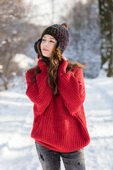On a winter sunny day, a young girl with long hair poses in a multi-colored knitted hat and a red sweater.