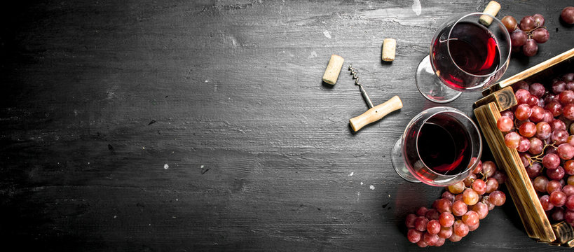 Wine background. Red wine in an old box with a corkscrew.