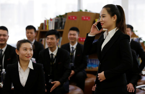 Member of JD.com's VIP delivery team practises calling a customer during a training session on business etiquette at the company headquarters in Beijing