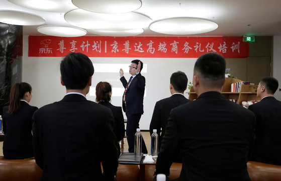 Members of JD.com's VIP delivery team attend a training on business etiquette in Beijing