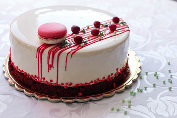 Tasty white homemade cake decorated by red berries and macaron