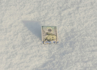 Banknote of an face value of one hundred dollars in the snow. Frozen Accounts. Bankruptcy. Concept