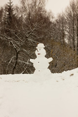 Snowman out of the snow, melting snow, spring background.