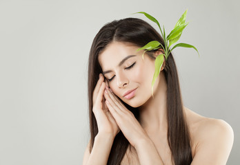 Beautiful Relaxing Woman with Green Bamboo Leaves on Head. Perfect Hair and Healthy Skin