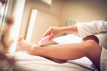 Depilation legs on bed. Morning is for body care.