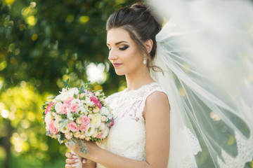 Beautiful bride a wedding dress play with a veil in the park