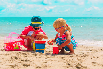 happy little boy and girl play with sand on beach