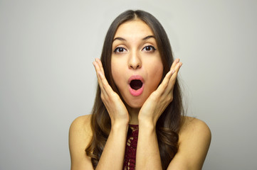 Surprised girl with open mouth and hands near the face on gray background