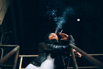 Young woman smoking a cigarette in abandoned industrial building