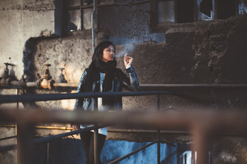 Young woman smoking cigarette in abandoned industrial building