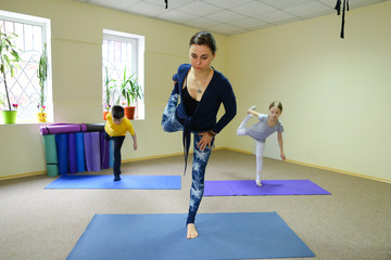 Little girl of European appearance engaged in gymnastics, child sitting on mat for fitness on twine, near trainer helps to perform exercises correctly. In background small child playing, trying to
