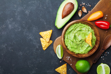 Guacamole dip with avocado, lime and nachos on black table top view. Copy space.Traditional mexican food.