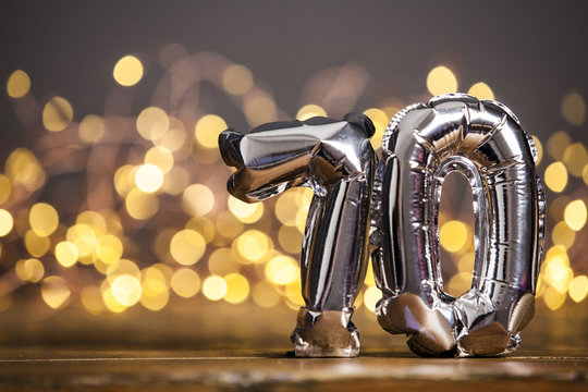 Silver number 70 celebration foil balloon against blurred light background