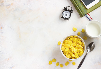 Corn flakes, coffee, alarm clock on a light background, breakfast