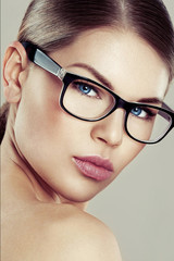 Fashion female in stylish eyeglasses over studio background. Eyesight correction concept.