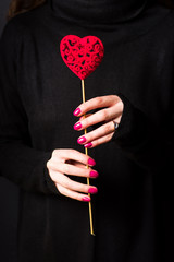 Female holding a heart shape wearing dark sweater