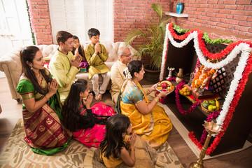 Indian  family performing Ganesh puja or Ganpati Puja in Ganesh Utsav, or holding ganesh idol over white background