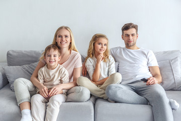 interested young family watching movie on couch at home