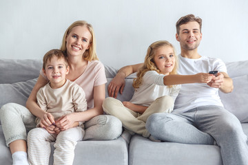 happy young family watching movie at home on weekend