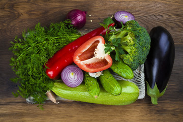 Heap of vegetables on cutting board over wooden texture background