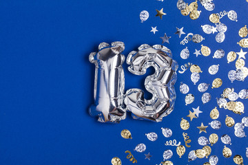 Silver foil number 13 balloon on a blue background with glitter gonfetti