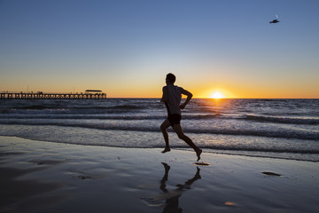 silhouette young dynamic athlete runner man with fit strong body training on Summer sunset beach running barefoot in sport healthy and fitness concept
