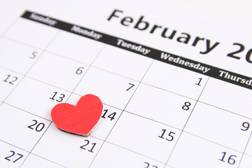Calendar page and red hearts paper on February 14 of Valentines day.