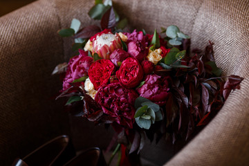 Top view on wedding trendy bouquet in red colors. Closeup of bridal flowers: peonies, protea, roses and greenery