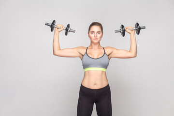 Happy blonde adult woman holding two dumbell, looking at camera