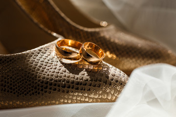 Wedding golden rings on the bride's shining shoes on a light background. Bridal trendy and expensive accessories, details