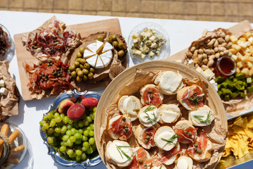 Salty and cheese bar of several kinds of cheese, grapes, olives, jamon, honey, nuts and snacks decorated on vintage wooden table. Wedding or other holiday party outdoors, picnic