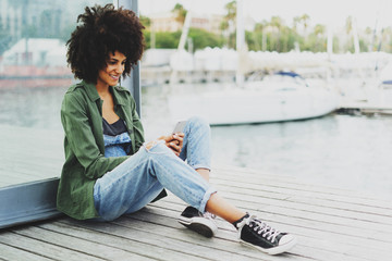 beautiful girl using mobile applications on her smartphone while sitting on a harbor in the port of a European city. Smiling girl looking at the camera on the phone while talking with friends