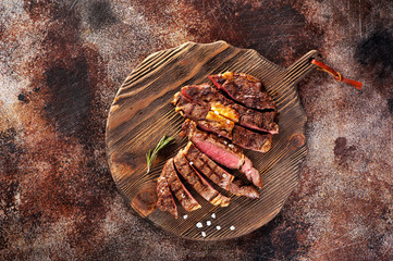 Ribeye steak slices on a wooden serving board on a concrete background