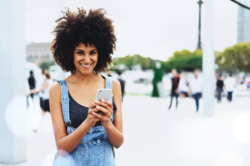 a beautiful dark-skinned smiley girl communicates in a group chat with friends through the application on the smartphone outside. Female traveler is guided in the city on the e-map in her cellphone.