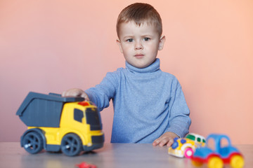 A cute little boy playing with model car collection. Toy mess in child room. Educational games for kids.