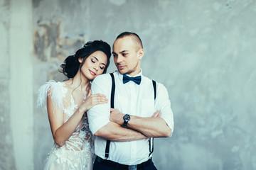 Happy bride and groom hugging in studio