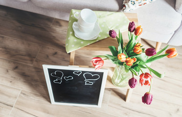 Cozy home spring atmosphere - vase with colorful tulips, chalk board and wooden chair