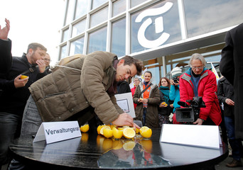 Striking employees of Schweizer Depeschenagentur (SDA) news agency squeeze lemons in front of the headquarters of publisher Tamedia, the agency's majority shareholder, during a demonstration against planned job cuts, in Zurich