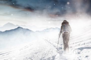 Sportliche Person wandert durch Schneesturm im Winter
