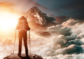 Bergsteigerin steht auf Gipfel und genießt Sonnenaufgang