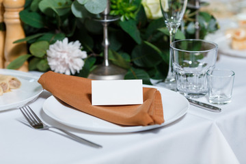 Wedding table setting with blank guest card, napkin, succulent and dish on a wooden plate. Rustic decor in brown tones