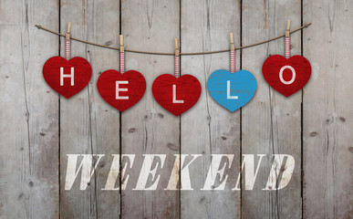 Hello weekend written on hanging red and blue wooden  hearts, on background of used weathered scaffolding wood
