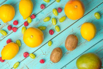 Fruits on rustic blue background. Kiwis, grapefruit, grapes, lemons and blackberries. Healthy food