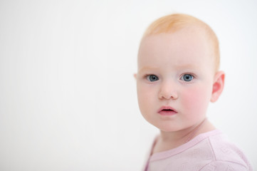 Baby girl in pink body looks at the camera on the white background