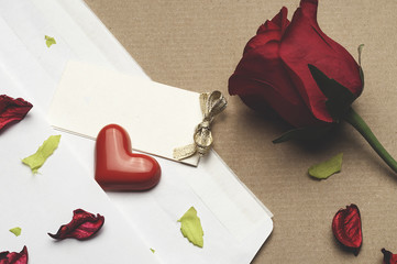 red rose in an envelope on a light brown background