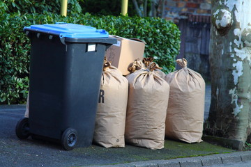 Rubbish can with blue hood and paper bags. Waste separation. Recycling in Germany.