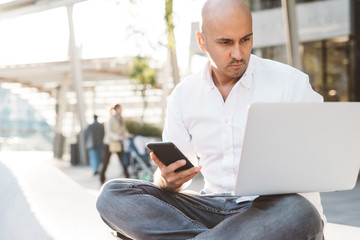 Young contemporary businessman remote working sitting outdoor in the city using computer and smart phone - portability, small business, networking concept