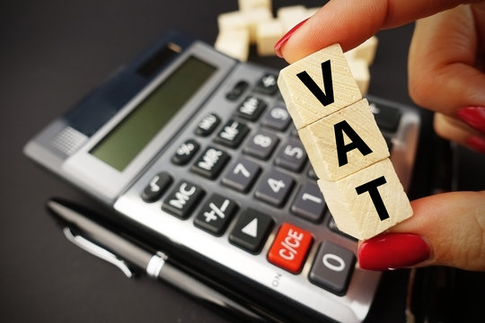 VAT text on wooden cubes above office calculator suggesting tax time or payment