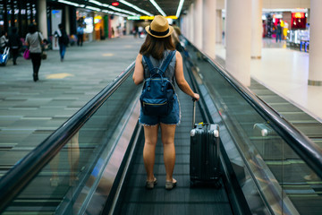 Young woman traveler in international airport with backpack holding suitcase