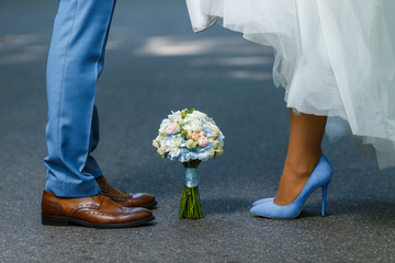 Wedding details: classic brown and blue shoes of bride and groom. Bouquet of roses standing on the ground between them. Newlyweds standing in front of each other